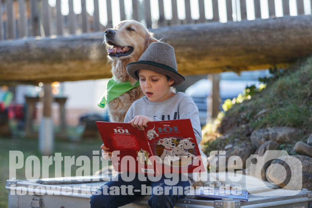 Hund Timber lässt sich von einem Kind eine Geschichte vorlesen