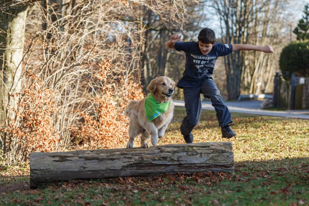 Hund Timber und Kind springen über einen Baumstamm