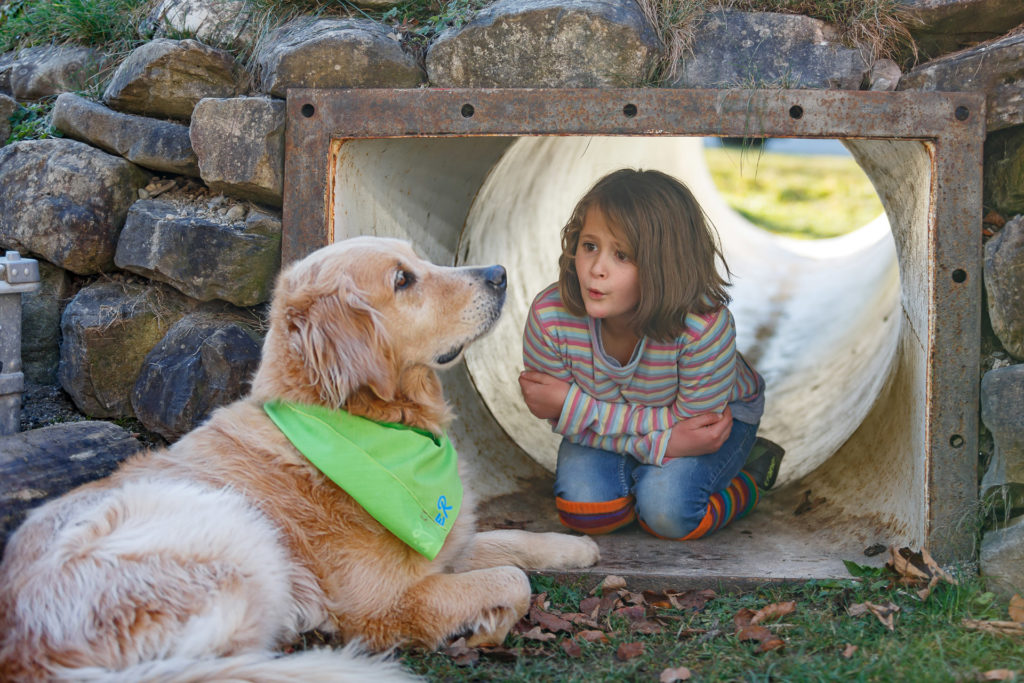 Kind sitzt in der Röhre und spricht mit Hund Timber