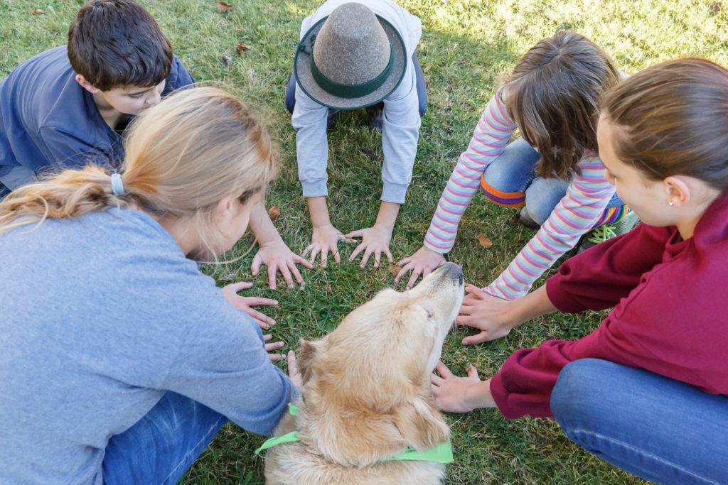 Hund Timber und Kinder sitzen im Kreis