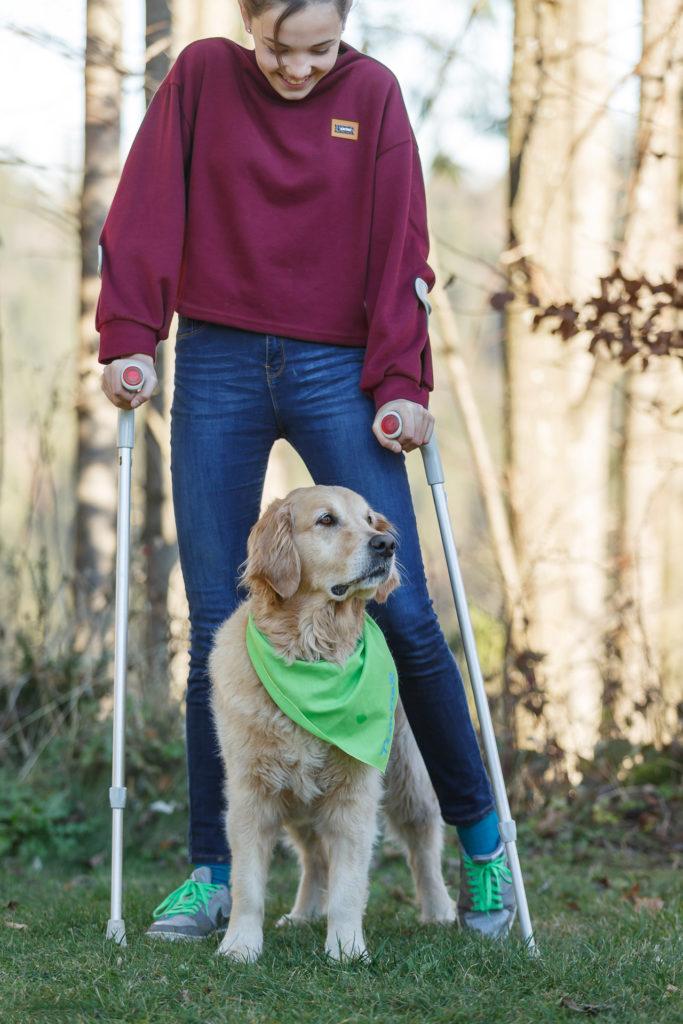 Jugendliche mit Krücken und Hund Timber