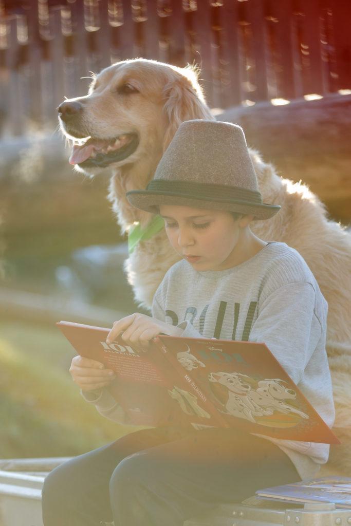 Kind liest Hund Timber etwas vor