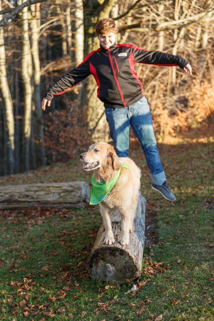 Hund Timber und Kind balancieren auf einem Baumstamm
