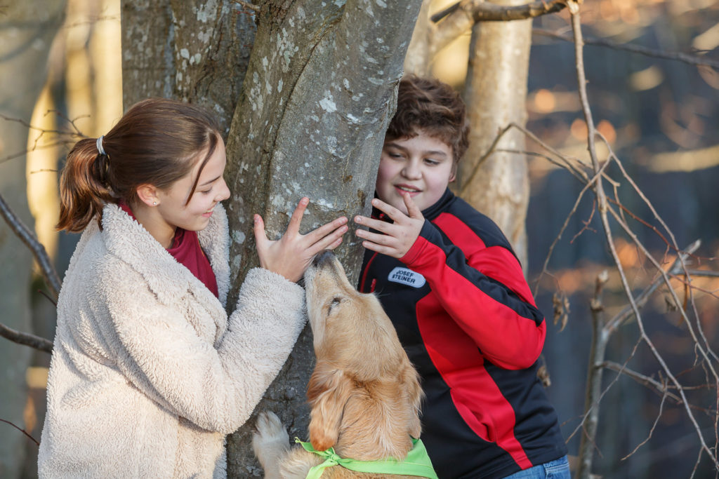 2 Kinder und Hund Timber neben einem Baum