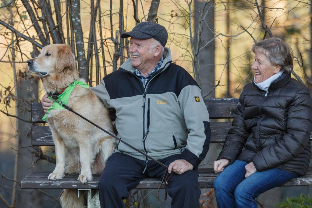 Hund Timber und Senioren Paar sitzen auf der Bank