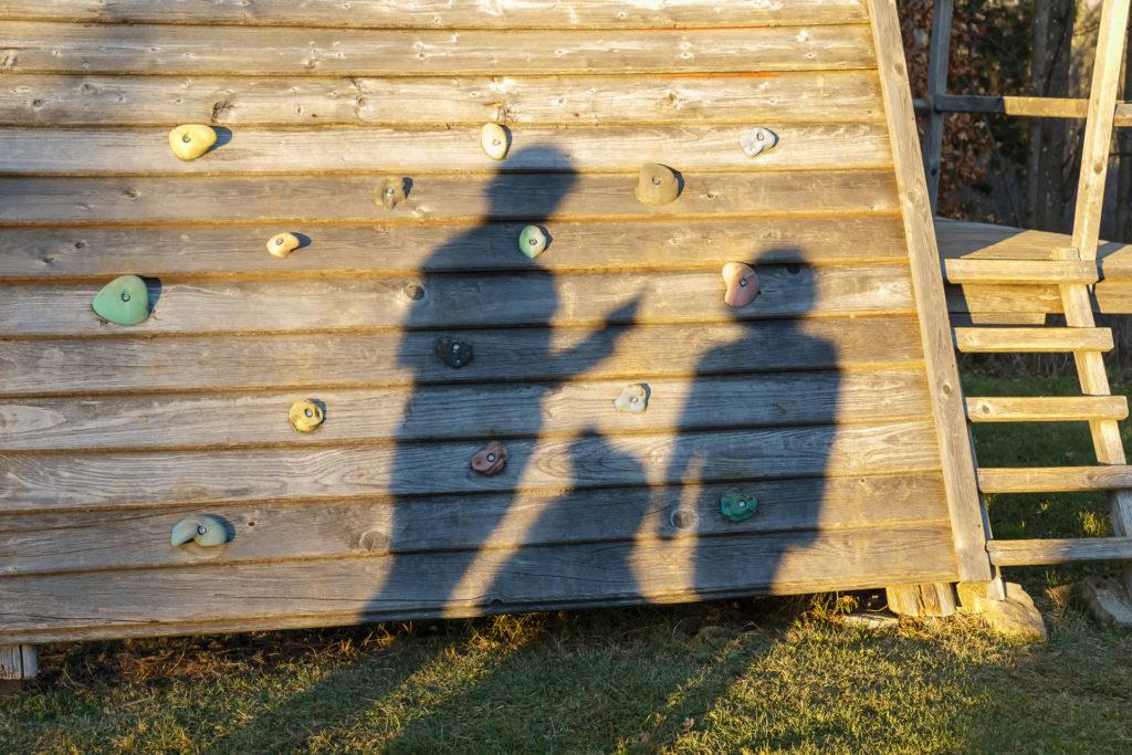 Schatten von 2 Kindern und Hund Timber an einer Holzwand