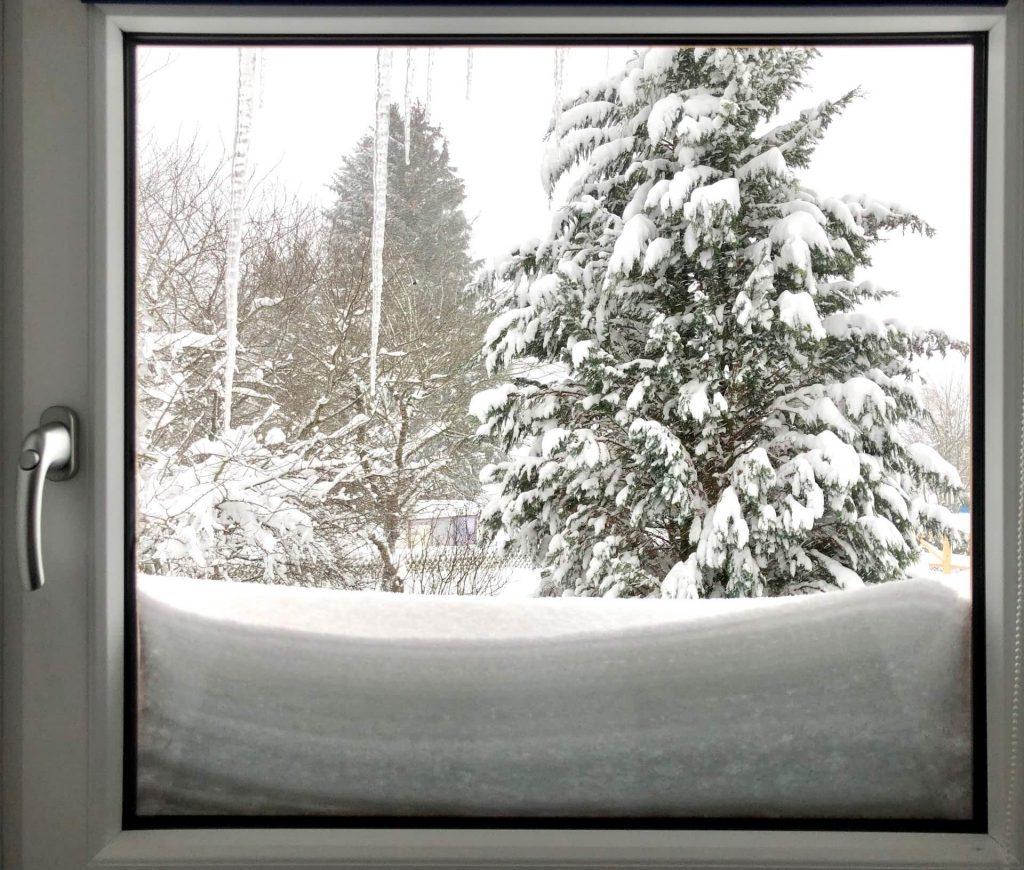 Blick aus dem Fenster in die Schneelandschaft