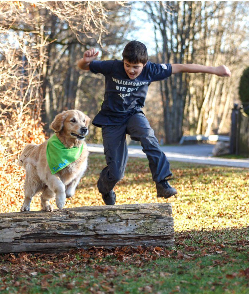 Timber und Kind springen über einen Baumstamm