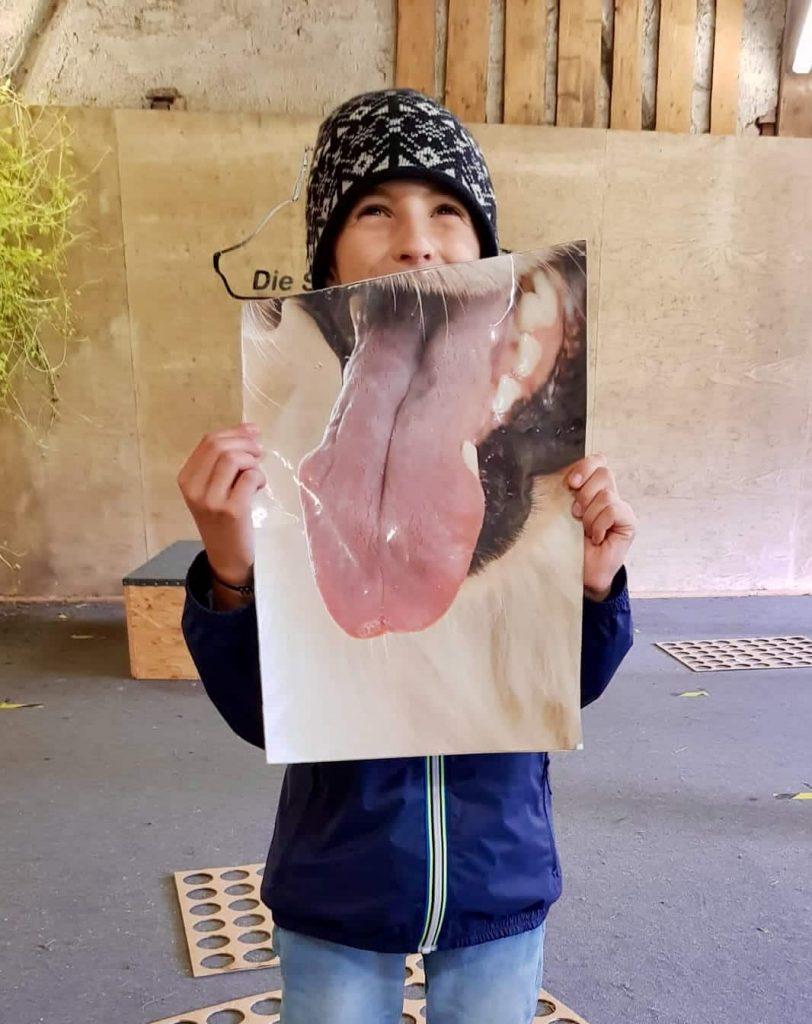Kind mit einem großen Bild einer Hundezunge
